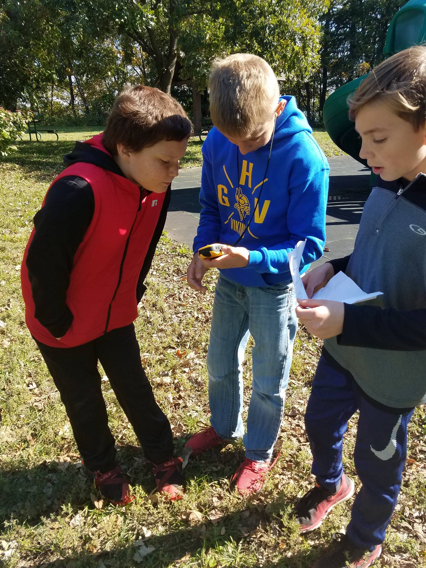 three students looking at GPS device for PBIS Celebration/DNR Day -  Fall 2017