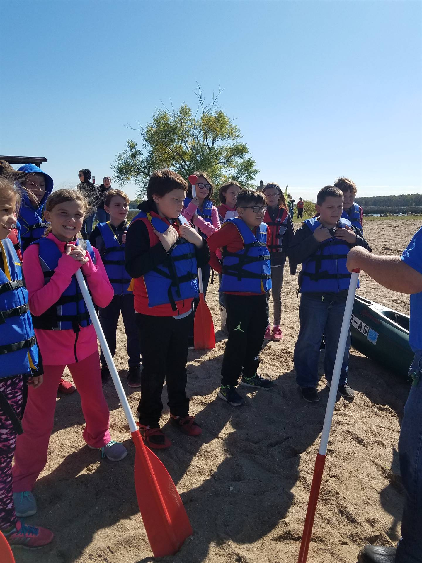 students standing on beach with life jackets and oars during PBIS Celebration/DNR Day -  Fall 2017