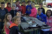 Students standing and sitting around picnic table