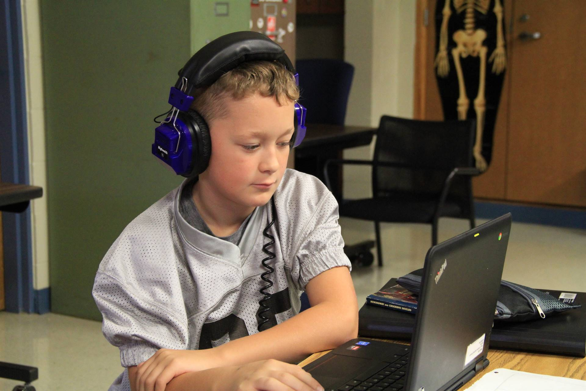 Boy looking at computer wearing headphones