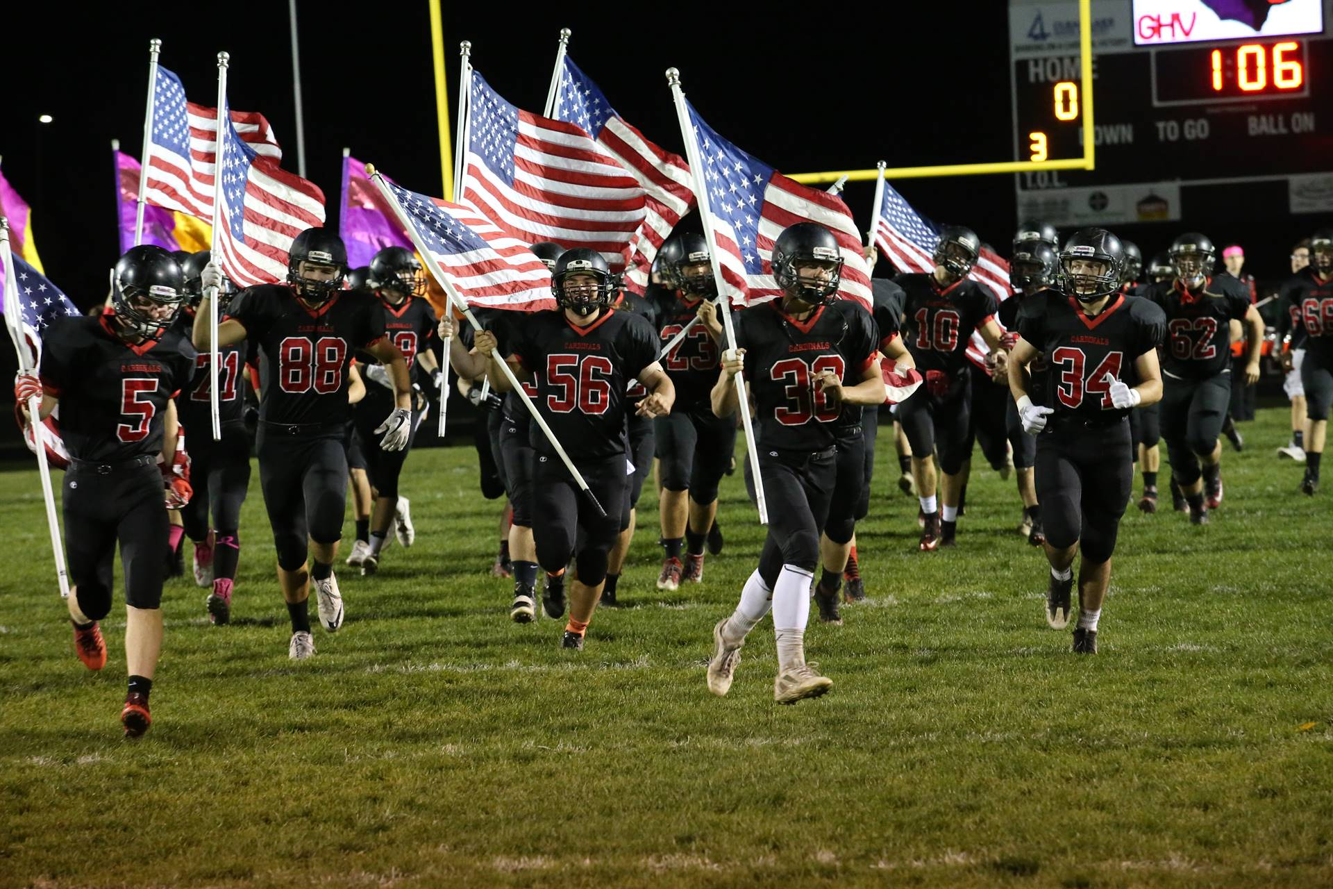 Football players running on field carrying American flags