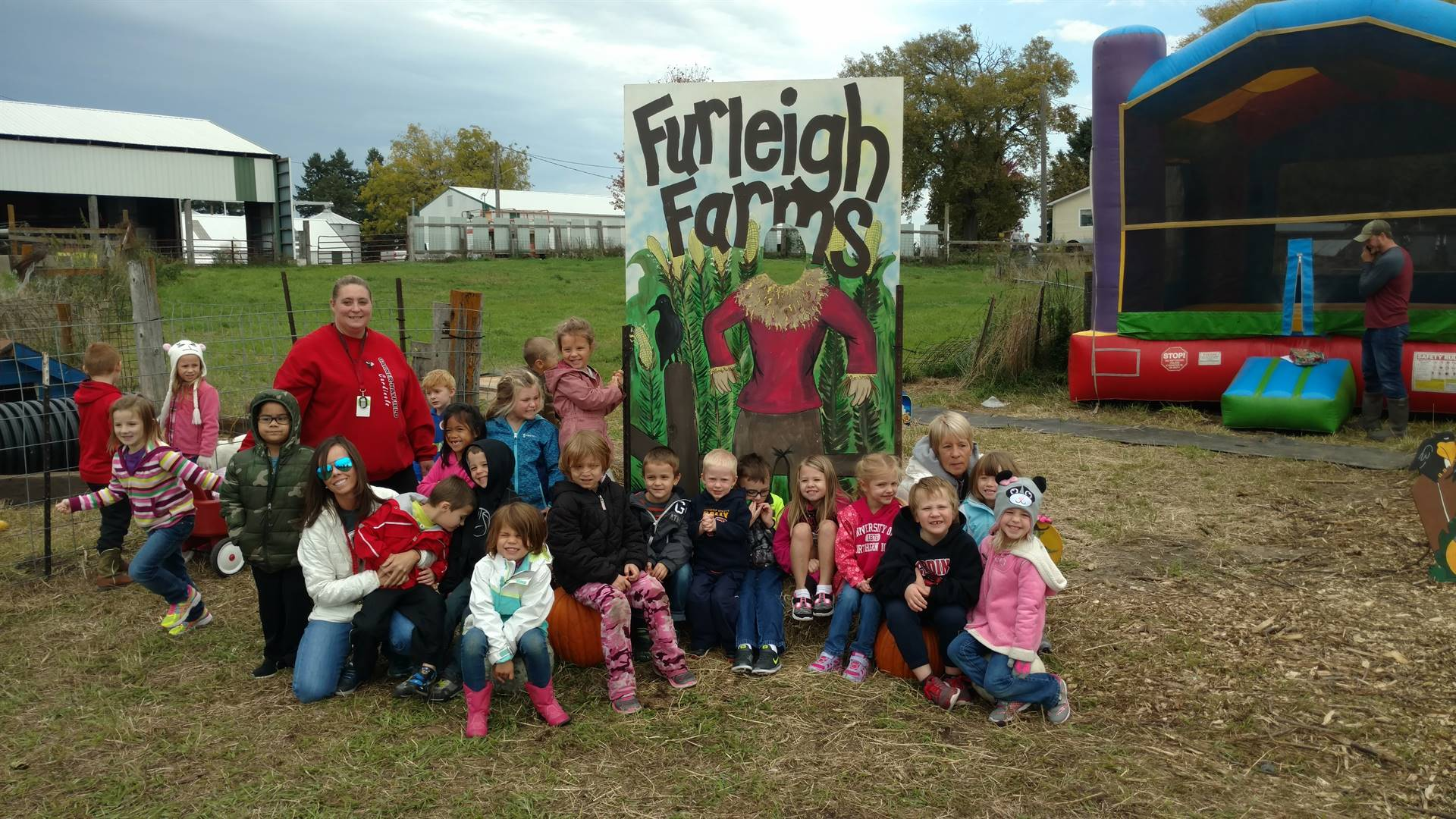 Students sitting near a Furleigh Farms Scarecrow Sign