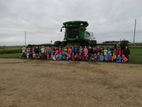 GHV First Grade Students visiting farm with a combine nearby
