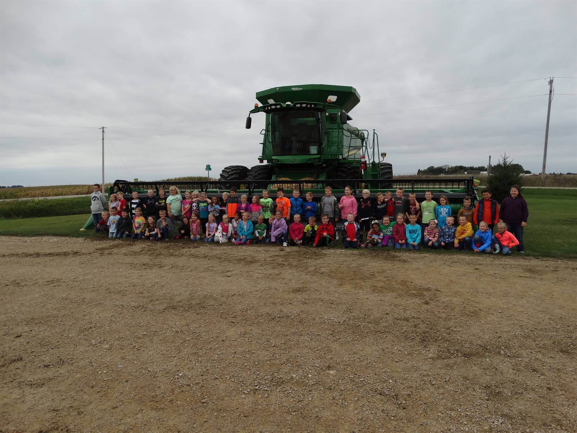 GHV first grade students class picture by a combine while on a farm field trip