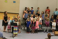 Second grade students standing on risers and singing