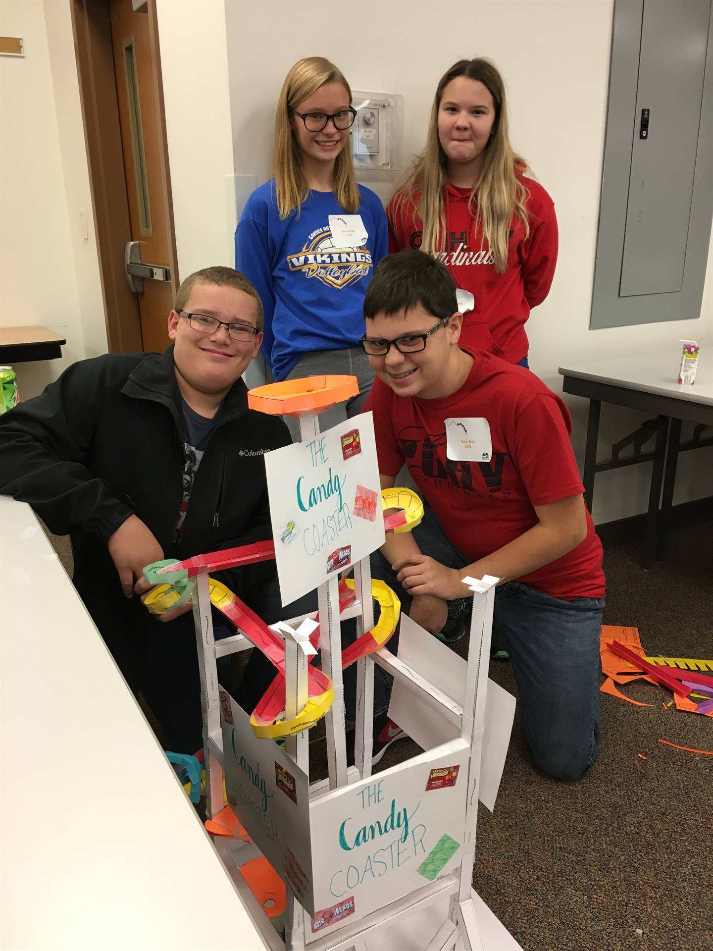 Students posing with a model-size roller coaster that they created