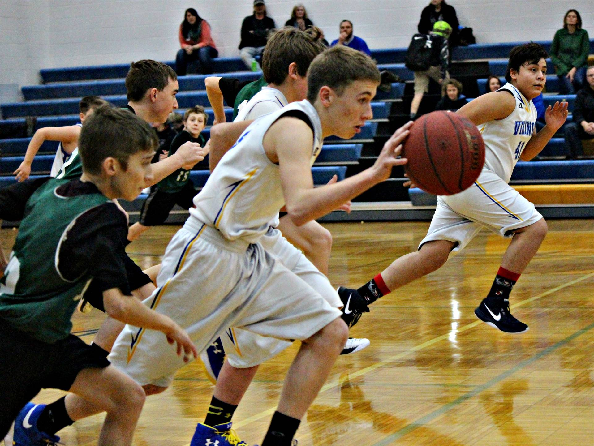 A group of boys playing in a basketball game