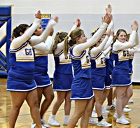 A group of cheerleaders cheering during a basketball game