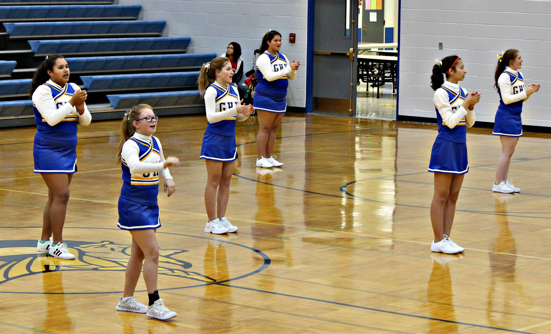 A group of cheerleaders cheering during halftime of a basketball game