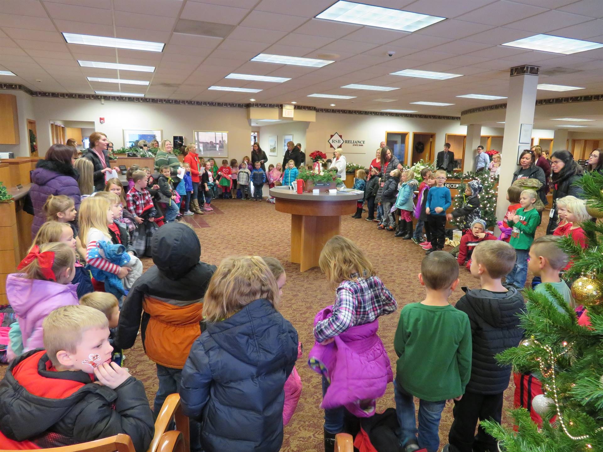 elementary students singing Christmas carols at local bank