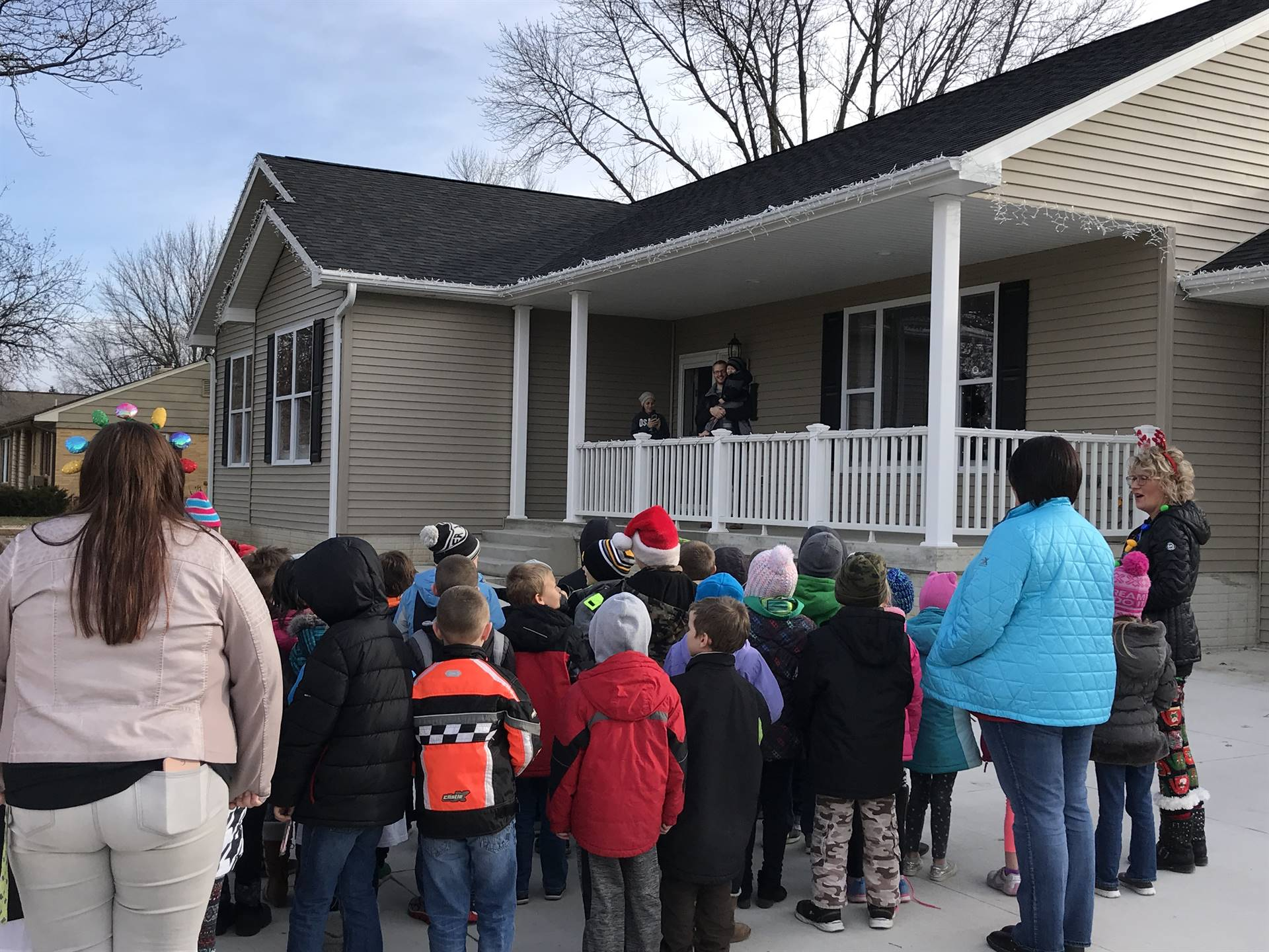 students standing outside of a home singing