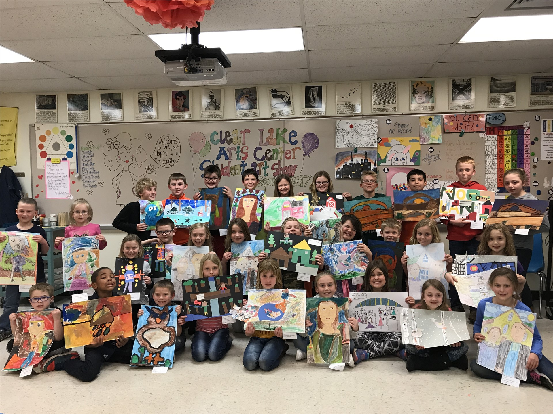 Elementary students holding their artwork