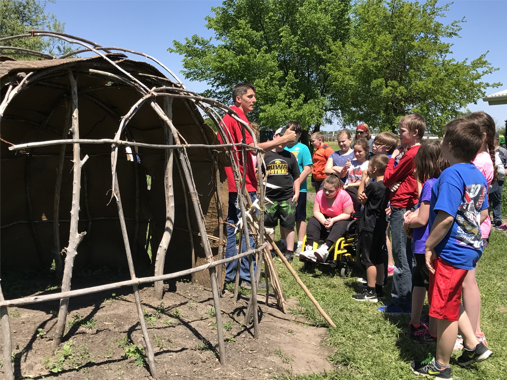 Students gathered around a Native American wickiup (home)