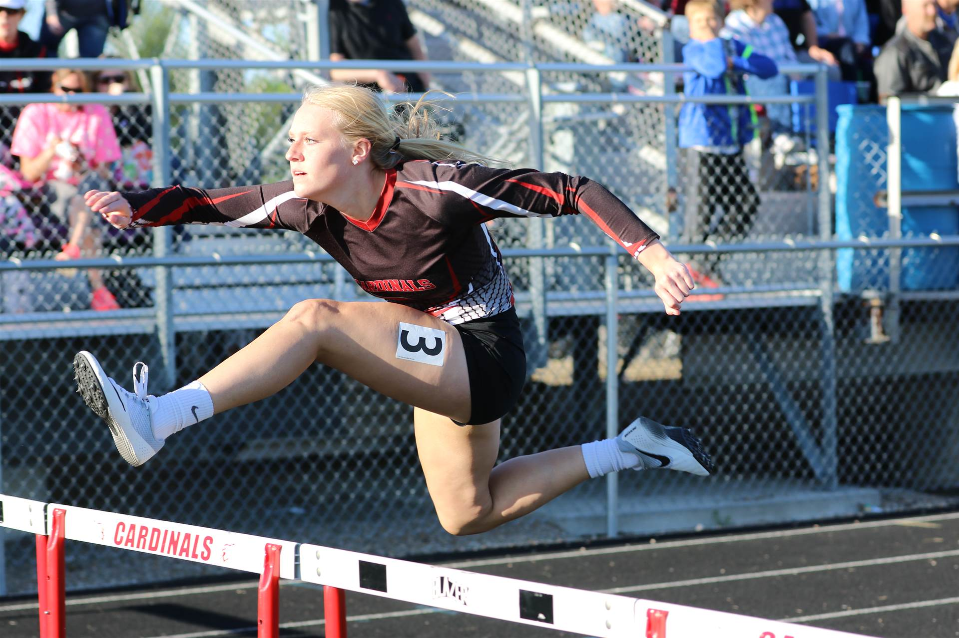 High school student hurdling a hurdle at a track meet