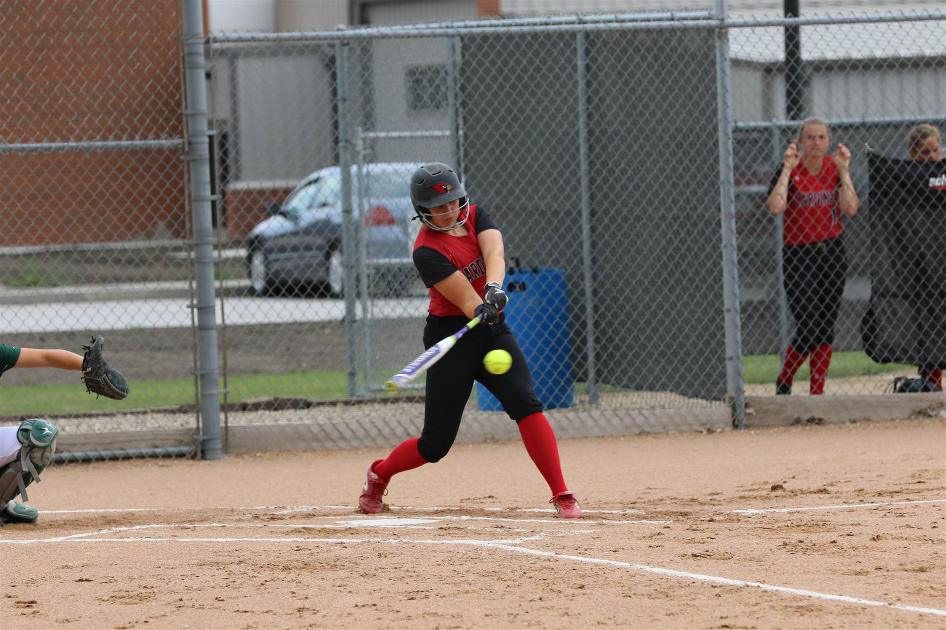 Softball player swinging a bat