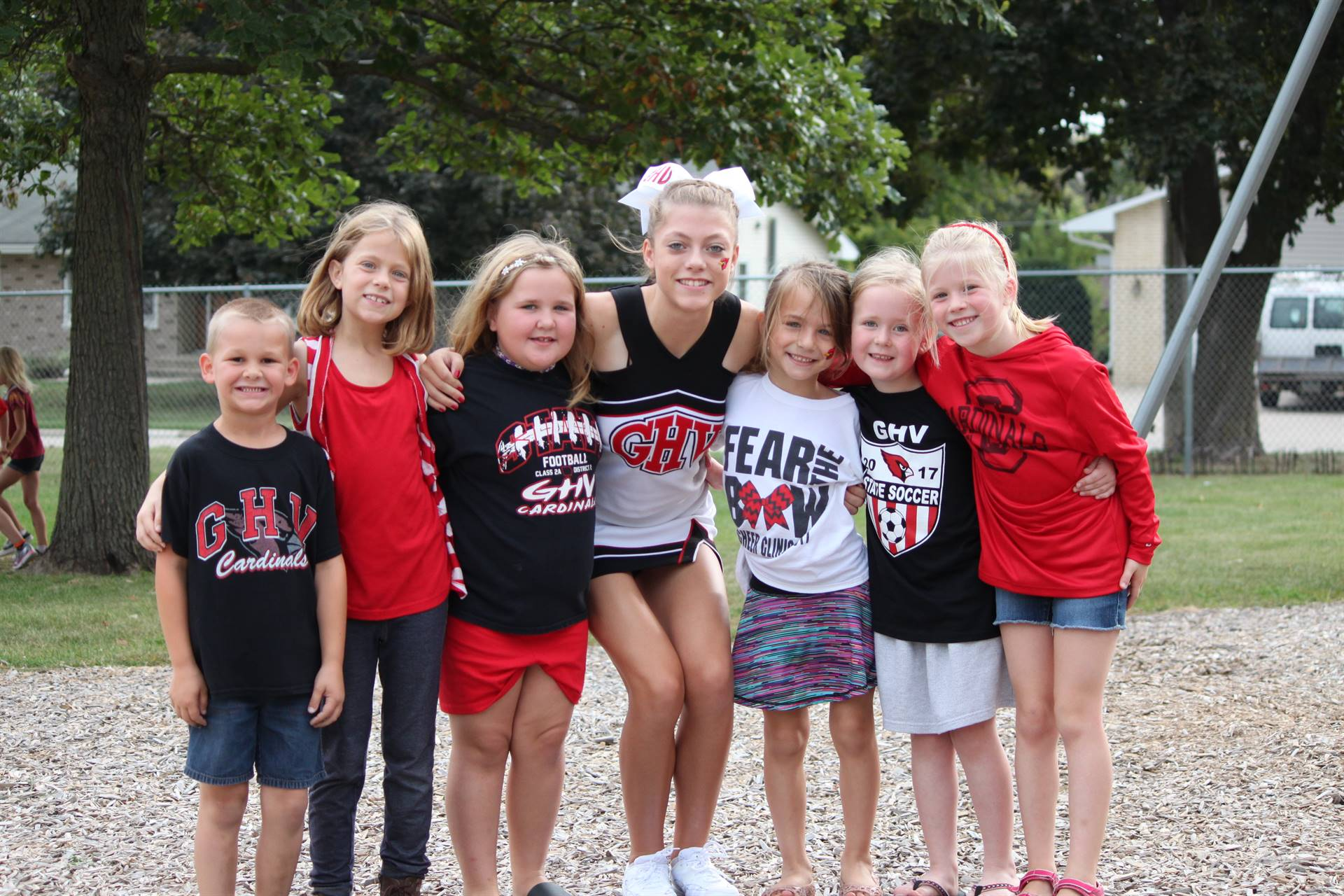High school cheerleader posing with elementary students on playground
