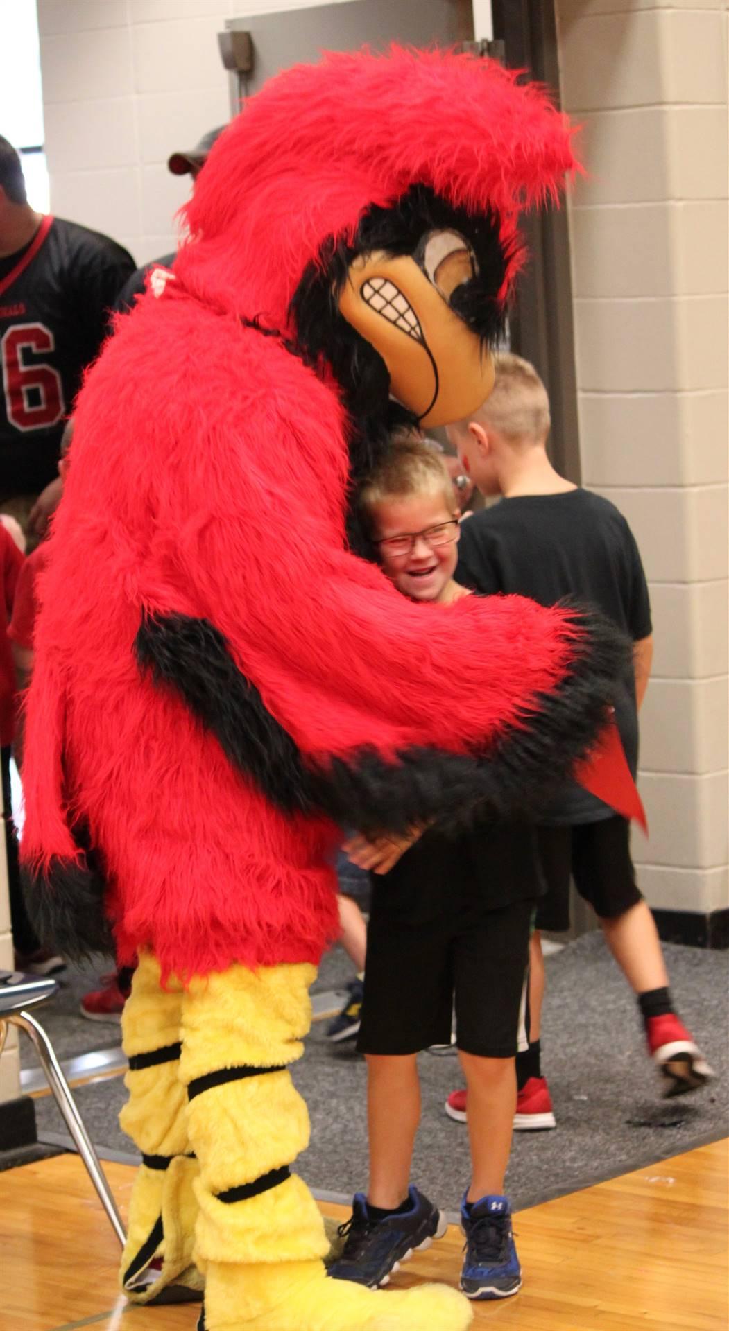 Cardinal mascot hugging elementary student