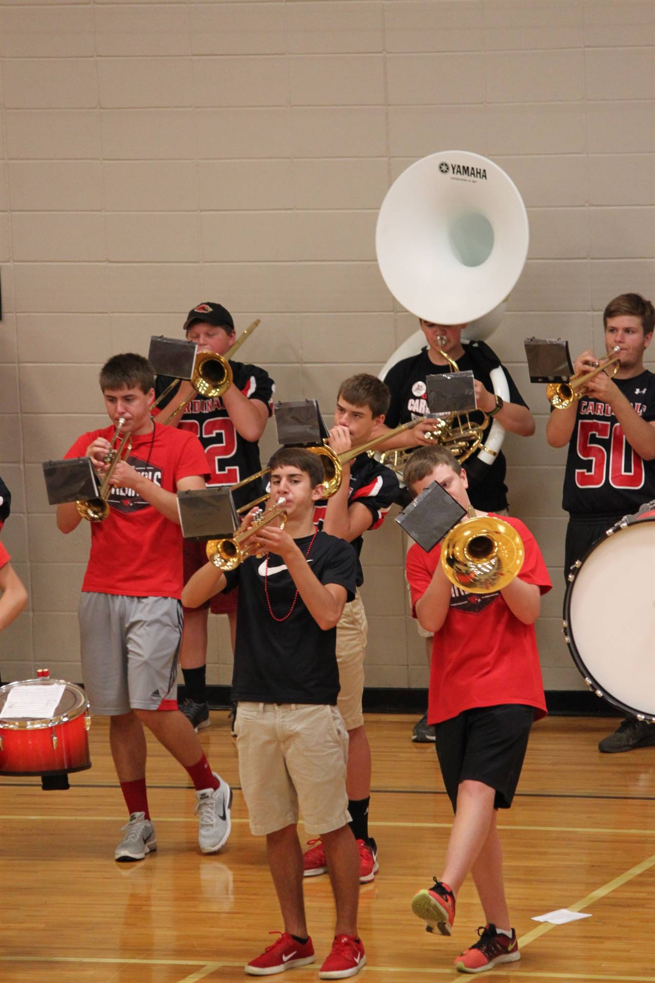 Students in a gym playing band instruments
