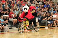 Two mascots riding a two-seater bicycle