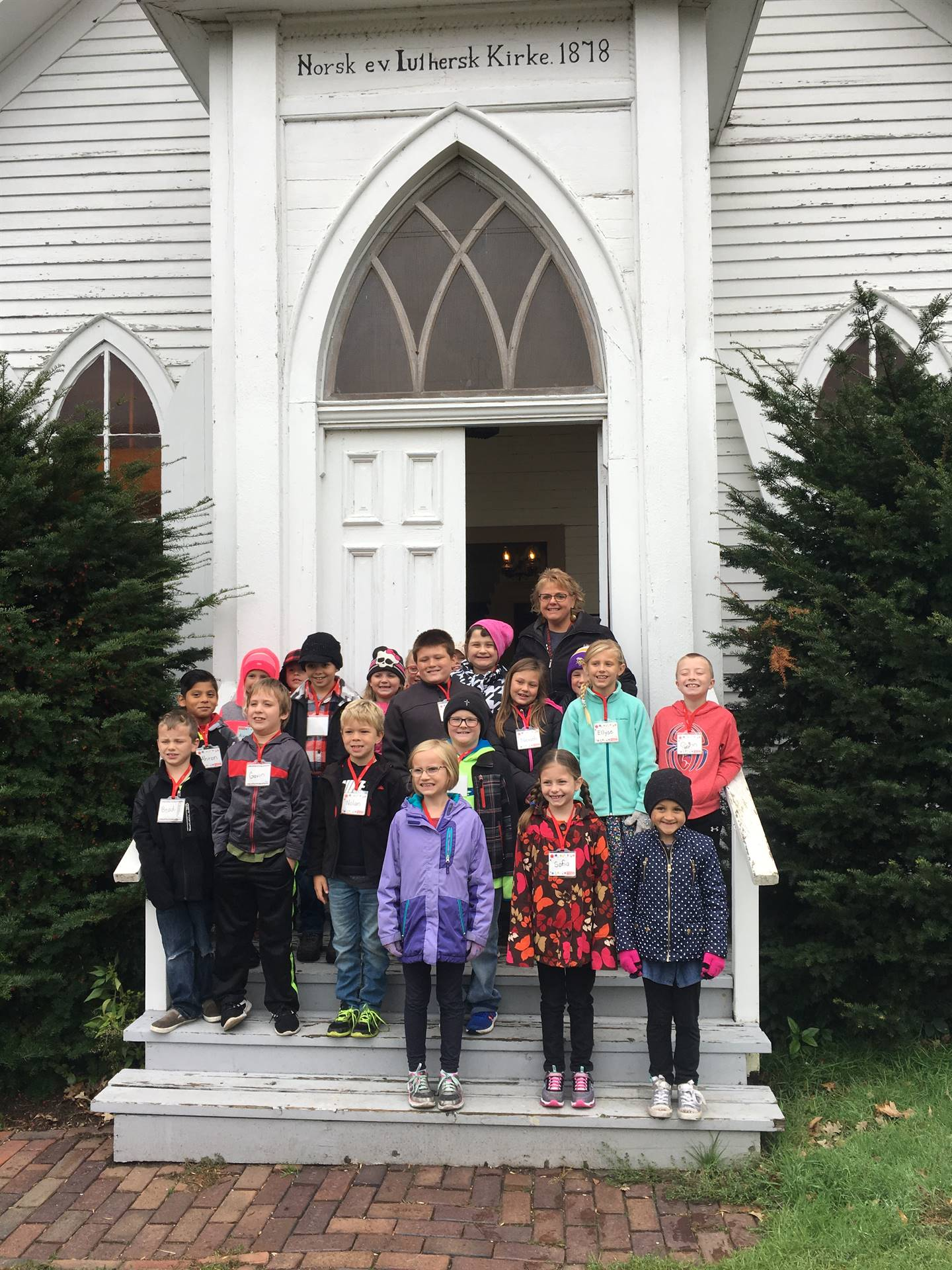 Second grade students standing on steps of old church