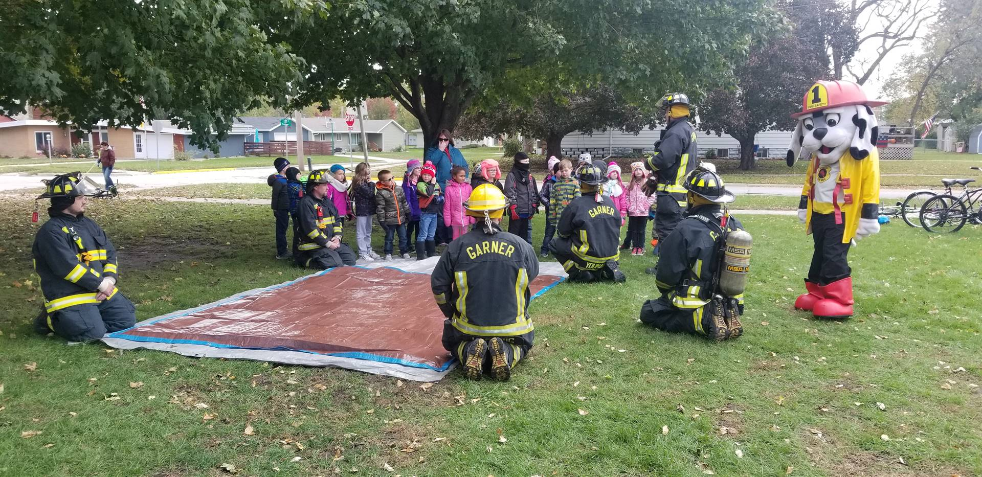 Students outside by a tree watching a demonstration on fire safety