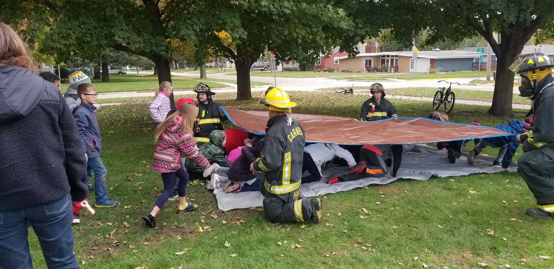 Students crawling under a tarp for fire safety practice