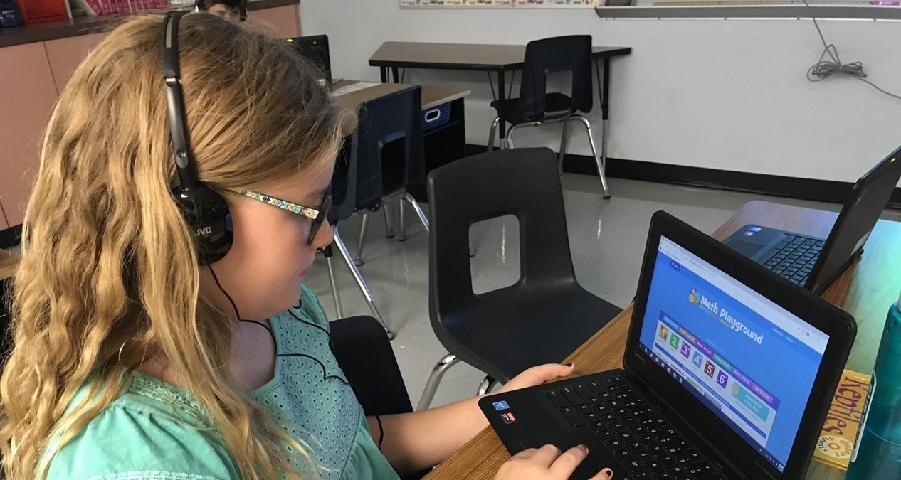 student at a desk with headphones and a laptop computer