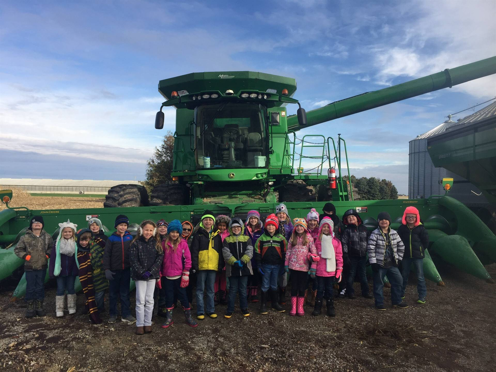 first grade students lined up in front of farm equipment