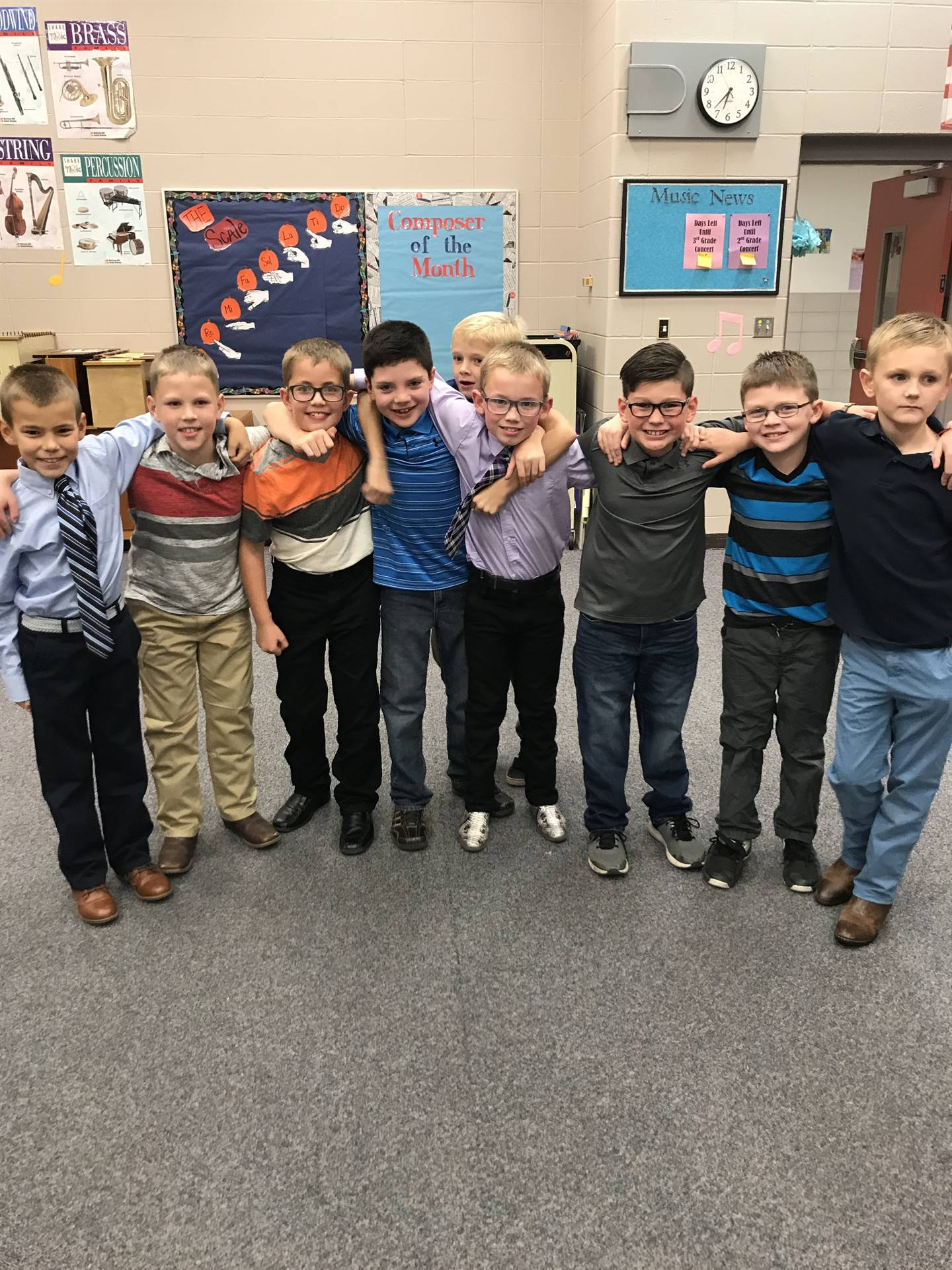 Third grade boys standing shoulder to shoulder and posing for a photo