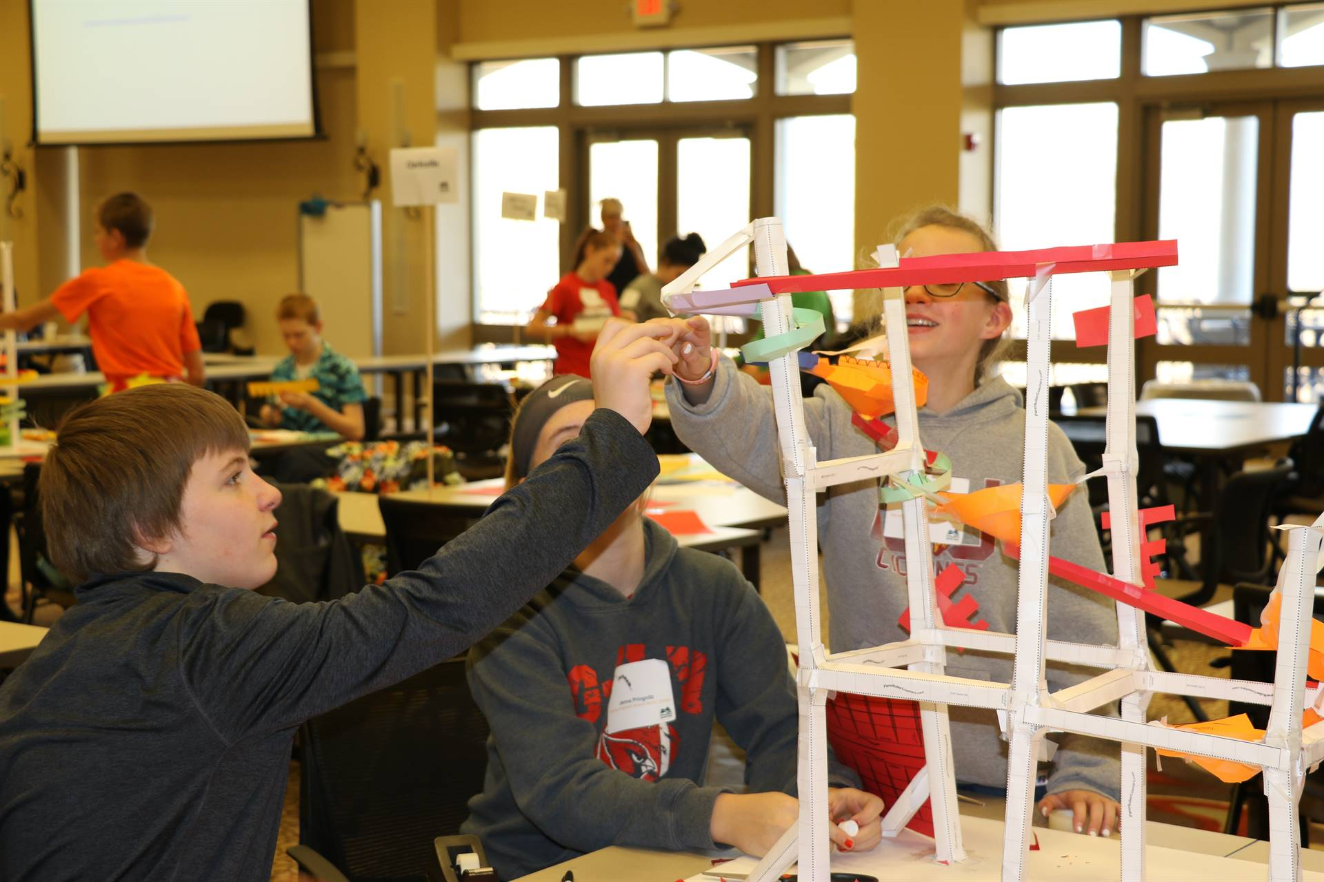 Students building a paper roller coaster for a competition