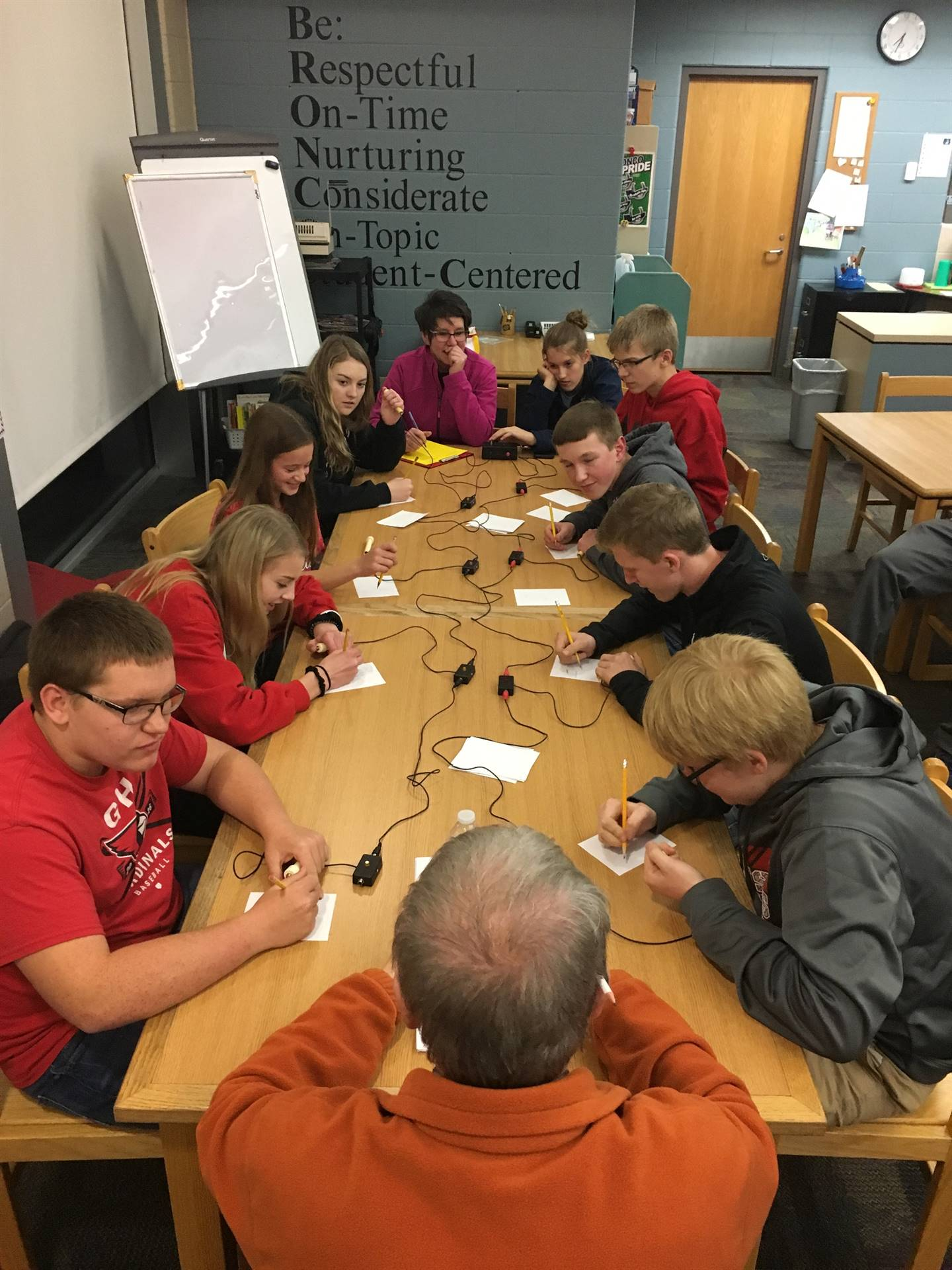 students sitting at a table with buzzers in hand for a quiz bowl