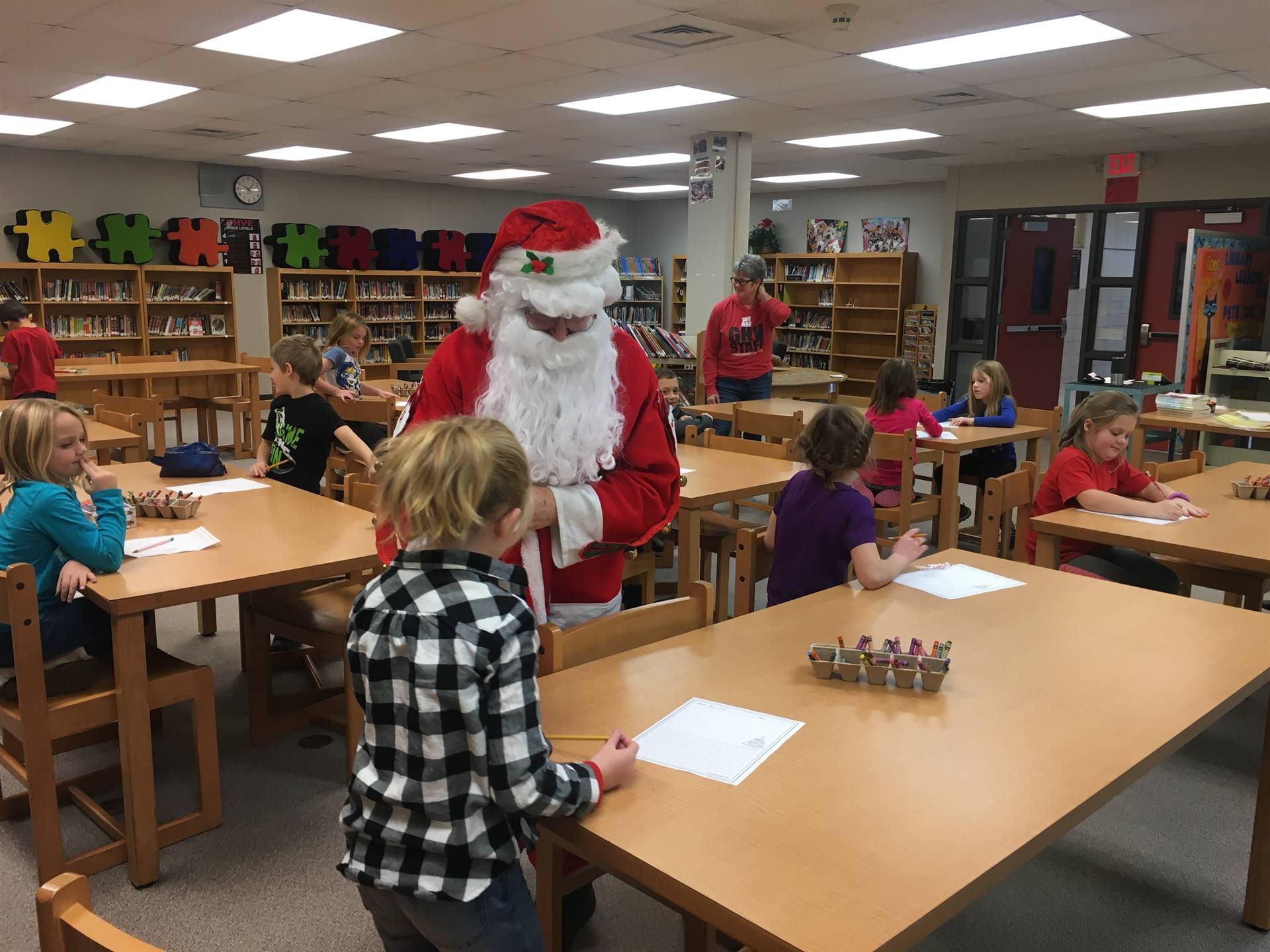 Santa Claus visits students in the elementary library