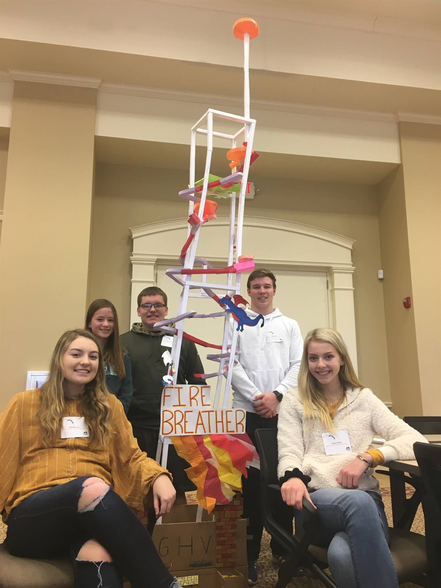 Students sitting around the paper rollercoaster they made at a roller coaster competition