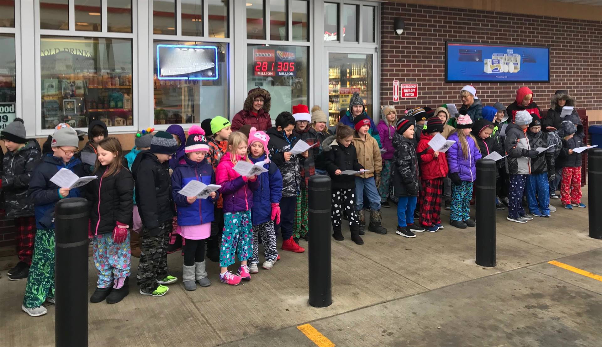 students singing outside of local business