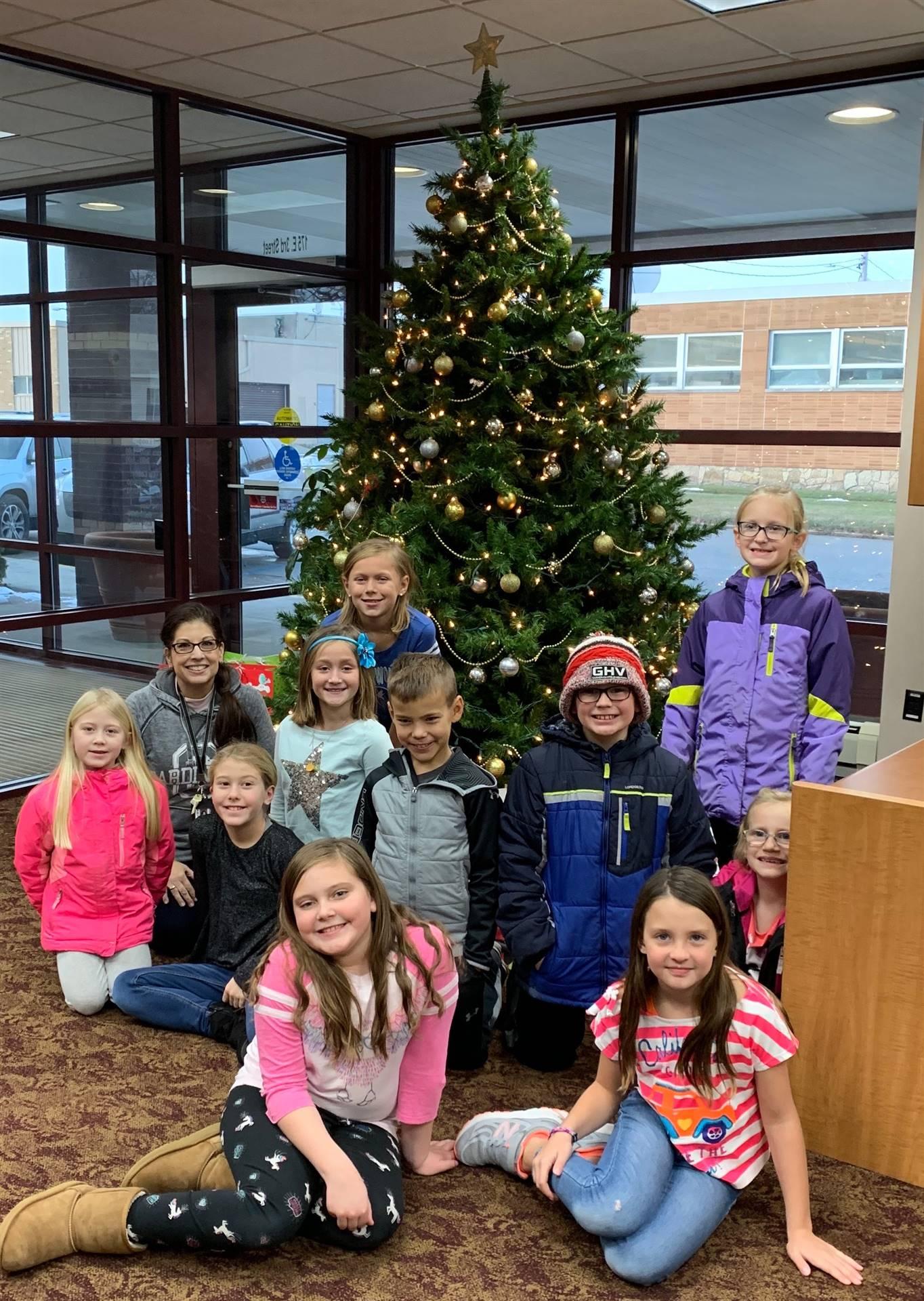 students sitting around Christmas tree