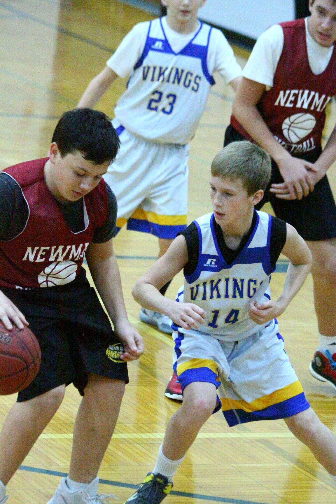 A boy dribbling the basketball while a defender guards him