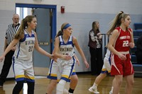 A group of girls playing in a junior high basketball game