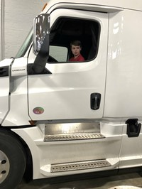 A student sitting in the cab of a semi at a career day