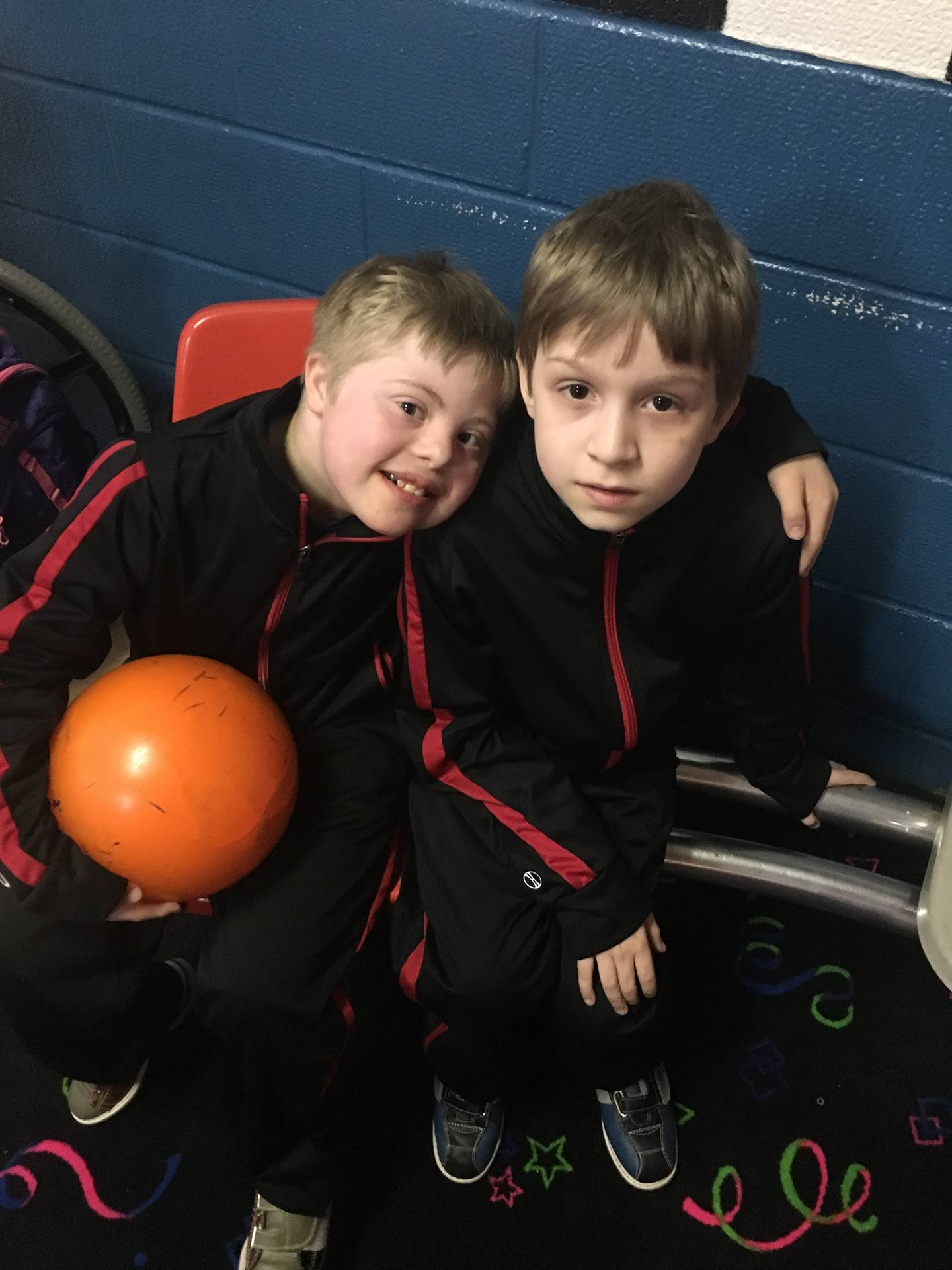Two students arm in arm with a bowling ball