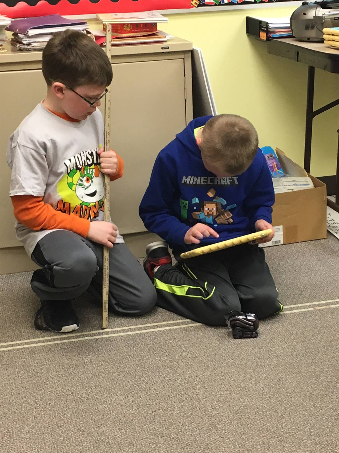 two students working with an iPad and a yard stick