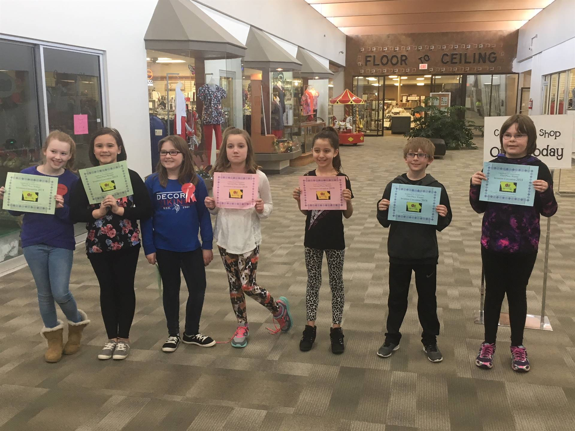 Seven elementary students standing and holding invention convention certificates
