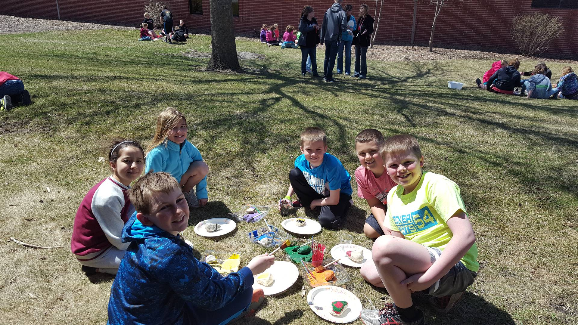 Students in a circle on the grass painting plates