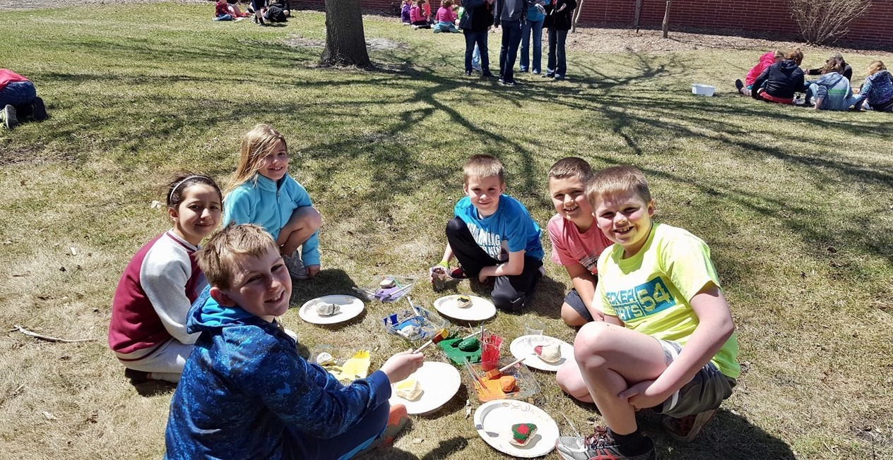 Elementary students sitting in grass working on artwork