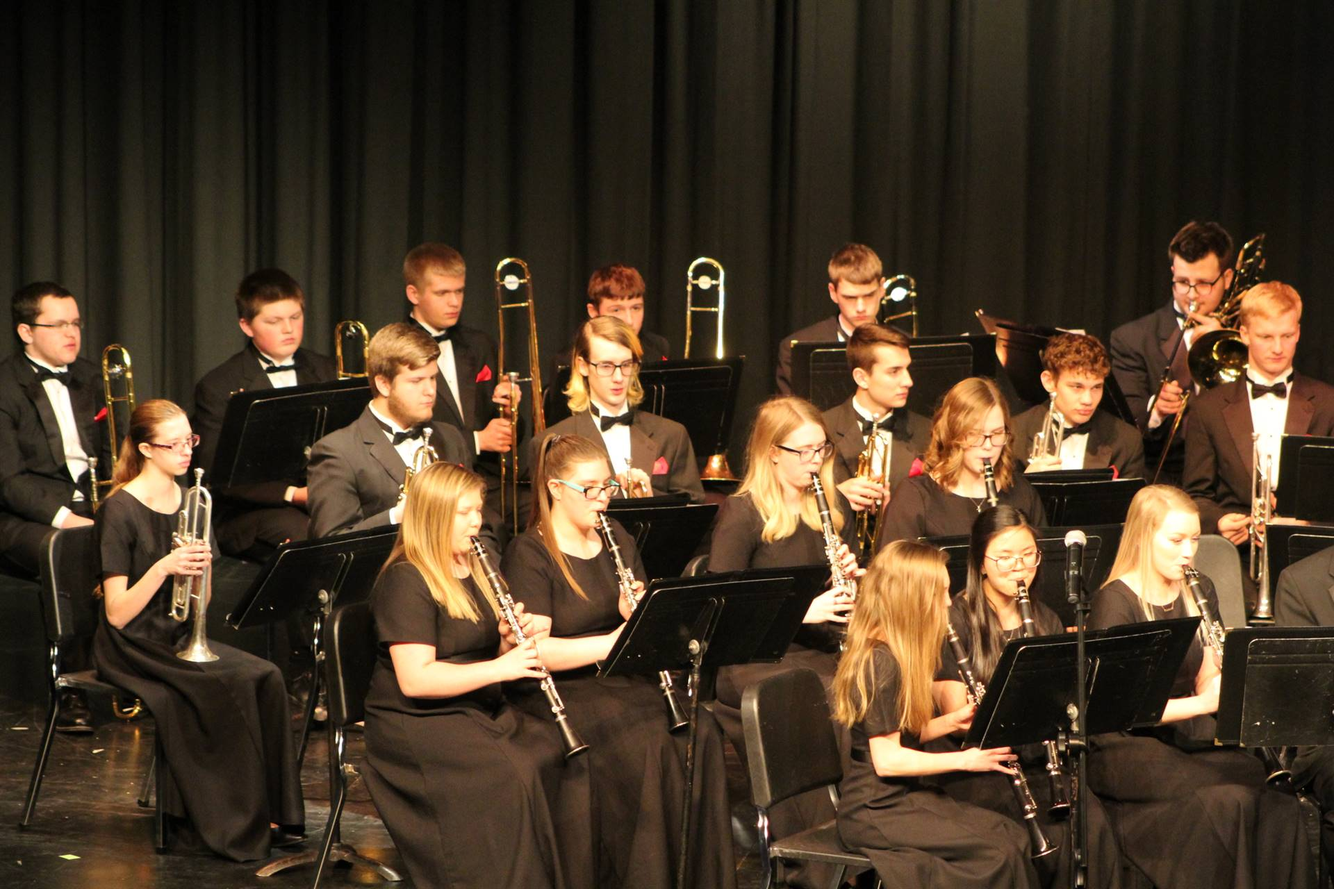 High school concert band students performing on stage