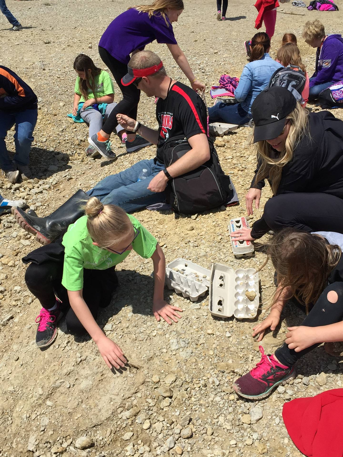 Students and teachers searching for fossils in a rock quarry