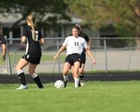 Soccer player kicks the ball away from an opponent