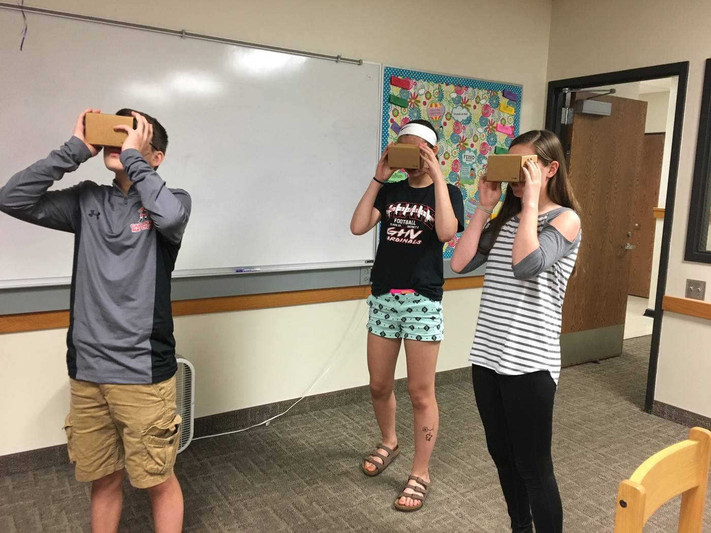 students looking into Google cardboard glasses