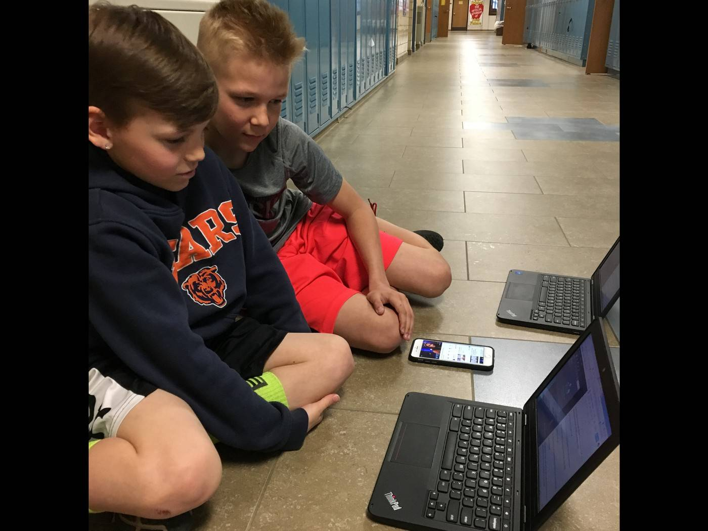 students sitting in hallway using cell phone and ChromeBook to create a pocast