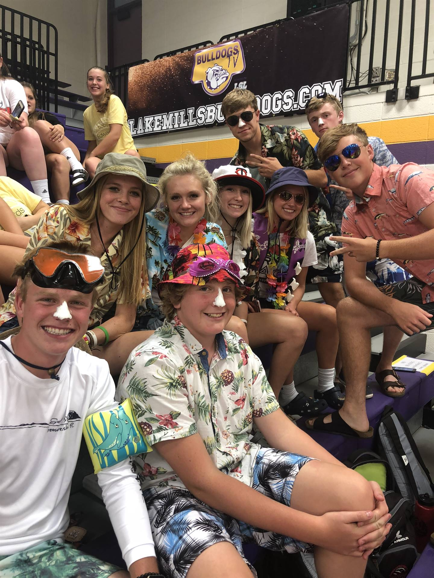high school students dressed in tropical clothing while in the bleachers