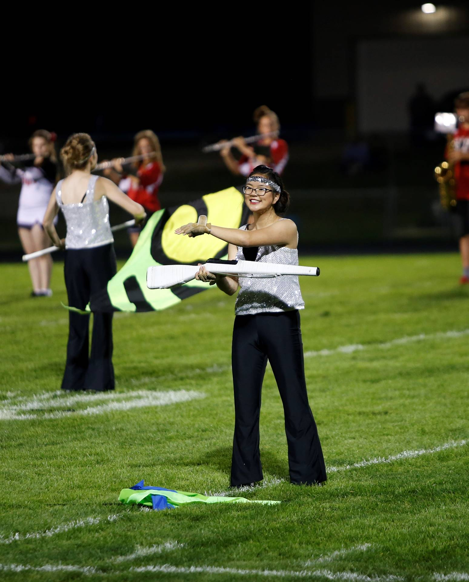 Girl performing on football field with flag